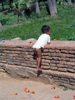 Inwa, spielender Junge in der Nähe einer Tempelanlage