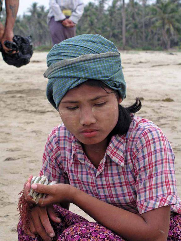 Ngwe Saung, junge Frau am Strand mit dem Ergebnis eines Fischfanges